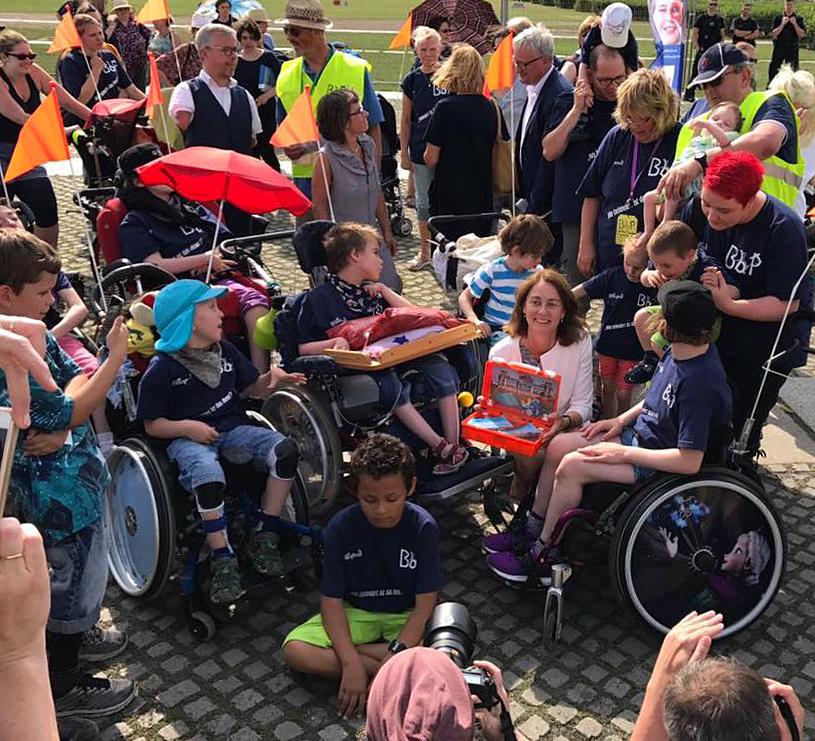 Bundesfamilienministerin Dr. Katarina Barley öffnet den BbP-Erste-Hilfe-Koffer im Kreis von Pflegekindern mit Behinderung und ihren Pflegefamilien.
