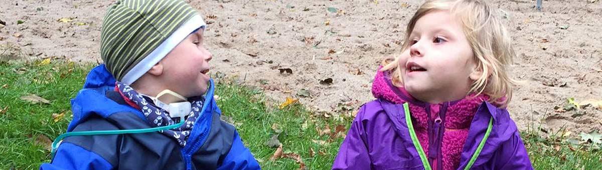 Zwei junge Pflegekinder, ein Junge und ein Mädchen, sitzen im Gras auf dem Spielplatz und lächeln sich an, im Hintergrund eine Sandfläche.