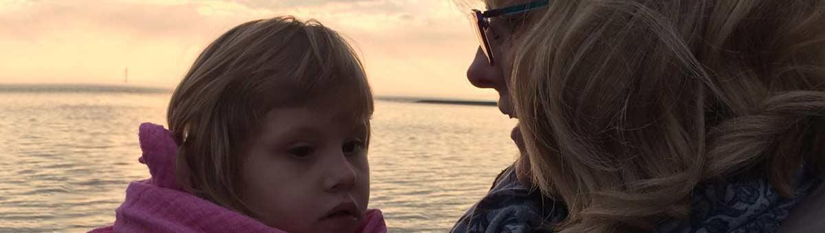 Ein junges Pflegemädchen bei seiner Pflegemutter auf dem Arm, im Hintergrund das Meer mit diesiger Abendsonne.