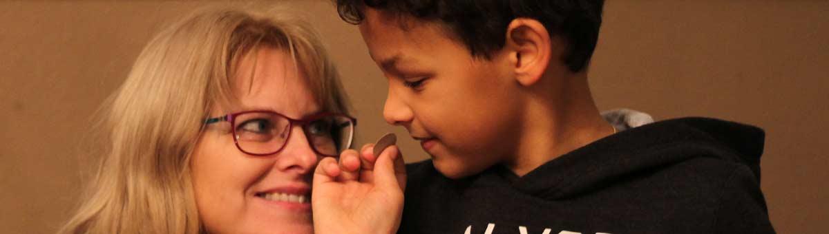 Eine Pflegemutter lächelt ihren Pflegesohn schräg von unten an; er zeigt ihr eine Münze dicht vor ihren Gesichtern.