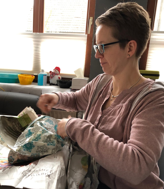 Mutter packt Geschenk aus