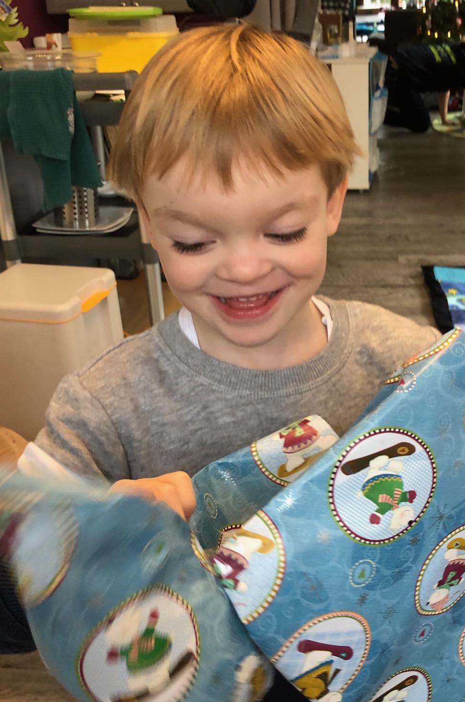 Junge packt Geschenk aus