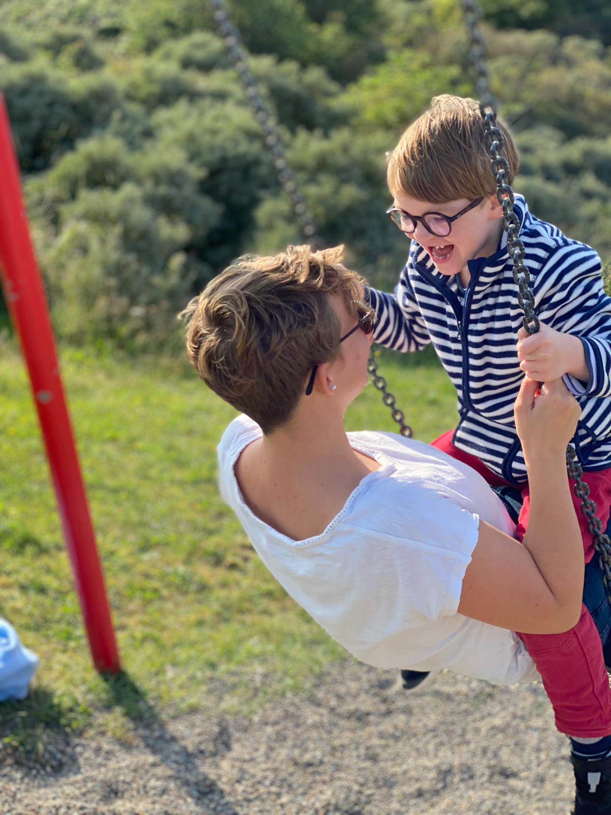Eine Frau schaukelt mit einem begeisterten Kind auf dem Schoß.