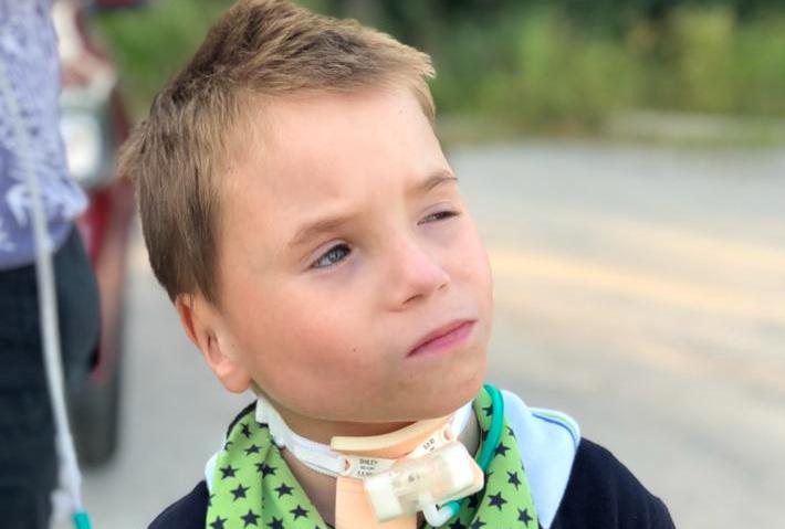Ein Kind mit Tracheostoma schaut skeptisch.